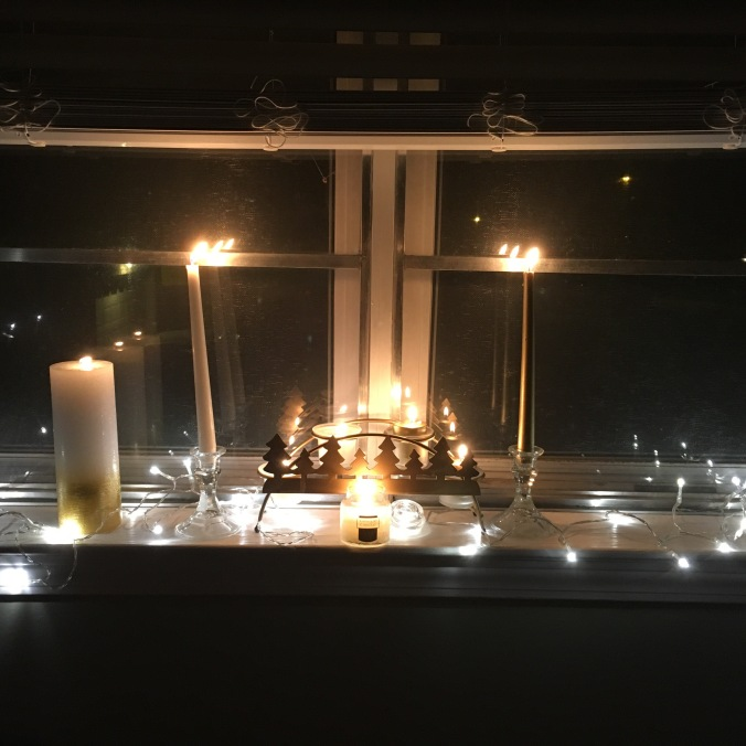 Image of an altar with candles on a white painted windowsill. On the far left is a large lit pillar candle, white at the top and fading to gold at the bottom. Next is a clear faceted glass candle holder holding a lit white taper candle. In the middle of the space is a gold arched candleholder with the silhouettes of pine trees on the front. This holds 4 lit votive candles; the left 2 are white, the right 2 are gold. In front of this sits a lit small white