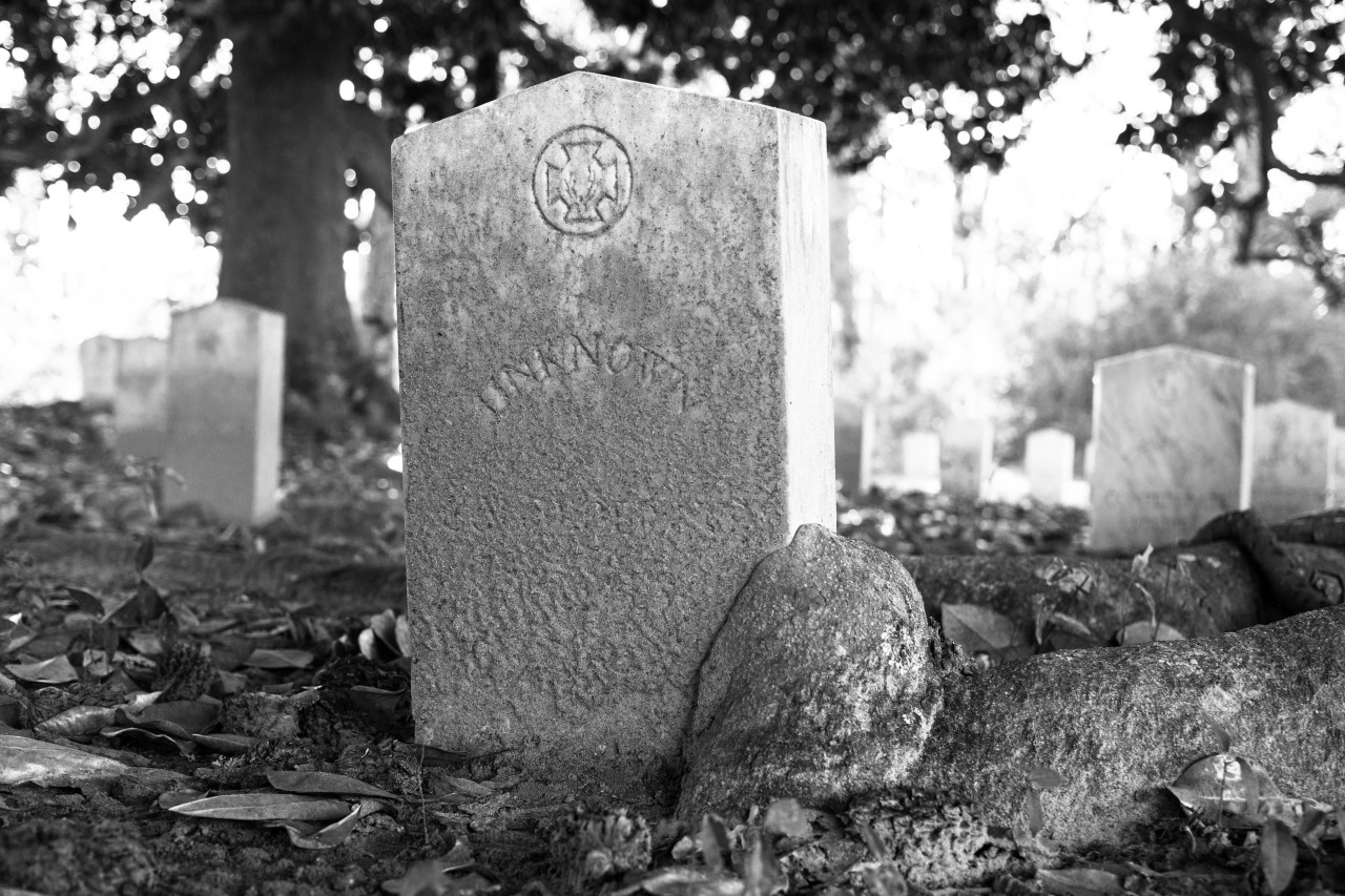 """A black and white photo of the grave of an unknown soldier in Friendship Cemetery, Columbus, MS, restin place of both Union and Confederate soldiers from the Battle of Shiloh. The grave marker itself stands upright, has a very slightly elevated point in the middle, and appears to have been white or light colored originally, but is now covered in a layer of grime. An equal-armed cross adorns the top and the word """"unknown"""" is written in large block letter along a curved line in the middle of the marker. A large, gnarled tree root buts up against and then grows up the bottom right corner of the stone. Other grave markers can be seen, blurred in the background."""