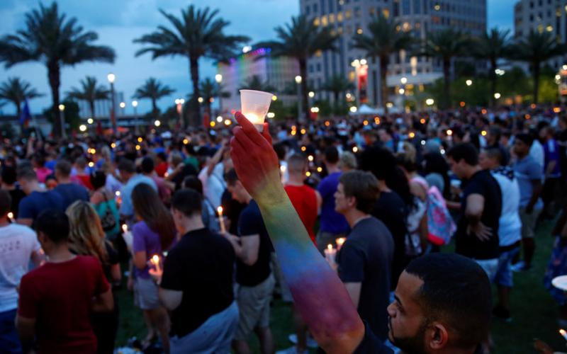 In a crowd of people golding candles, a masculine person's arm with a medium brown skin tone is painted in the colors of the rainbow and is outstretched holding a candle in a plastic cup. There are many more peopl ein the background holding candles and there palm trees and tall buildings with rainbow lights in the far background.