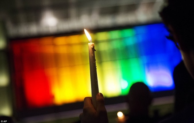 A single while taper candle is burning in the center of the fram, held by a hand that is at the bottom of the frame and the edge of the back of someone's head on the right of the frame. In the background, blown out lights in the colors of the rainbow fill most of the image.