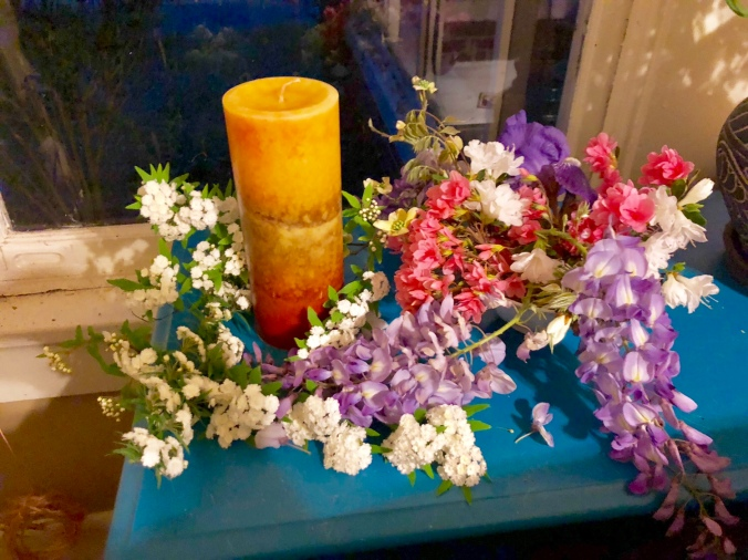 An image of Áine's shrine. A y'all candle in summer shades of yellows, oranges, and a few reds is surrounded by pink and white azalea blooms, a purple iris, unknown small white flowers in clusters on branches, and cascades of wisteria, all on a teal table. There is a window behind that is dark, reflecting the light from inside the house. Photograph by author.